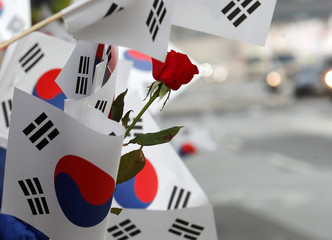South Korean flags and a flower is seen waved by people as a convoy transporting South Korean President Moon Jae-in leaves the Presidential Blue House for the inter-Korean summit in Seoul
