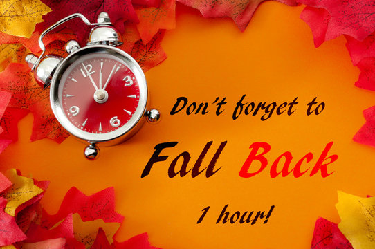 Fall back, the end of daylight savings time and turn clocks back on hour concept with a clock surrounded by dried yellow leaves with the text Don't forget to fall back on hour