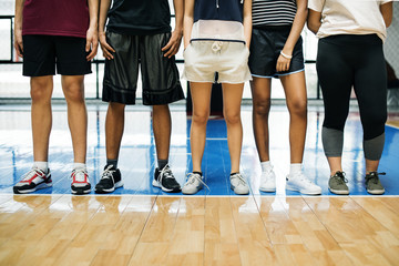 Group of young teenager friends on a basketball court standing in a row