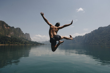 Man jumping with joy by a lake Wall mural