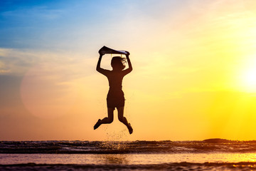 slim woman holding surfboard in hand put in the air over the head, jumping on the sea beach looking forward to see the sufficient wave to surf at sunset scenery light