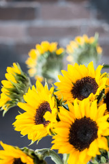 Bouquet of bright sunflowers on a wooden table.