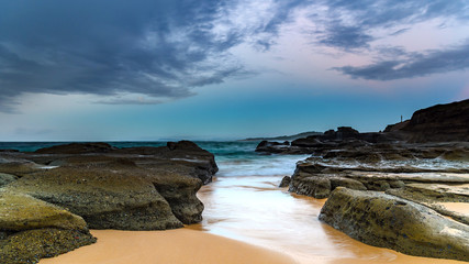 Rocky Shore and Overcast Sunrise Seascape