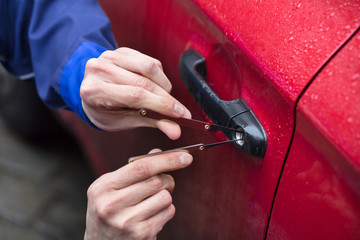 Person Opening Car Door With Lockpicker