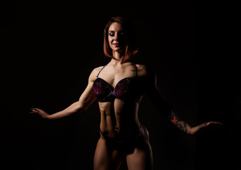 attractive fitness woman, muscles young athlete on dark background