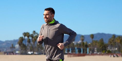 fitness, sport, people and healthy lifestyle concept - happy young man running over venice beach background in california