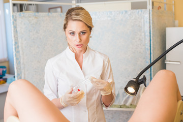 Friendly female blonde hair doctor gynecologist is working with patient