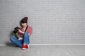 Young female photographer with camera near brick wall