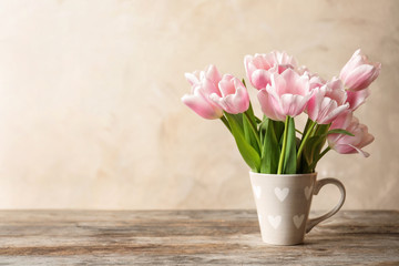 Cup with beautiful tulips for Mother's Day on table