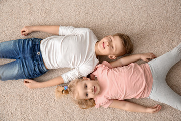 Cute little children lying on cozy carpet at home, top view