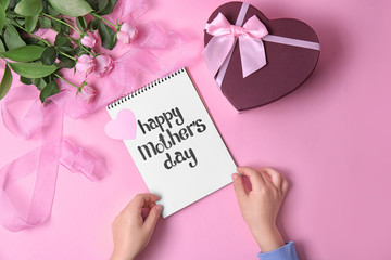 "Child holding notebook with phrase ""HAPPY MOTHER'S DAY"" near gift and roses on table"