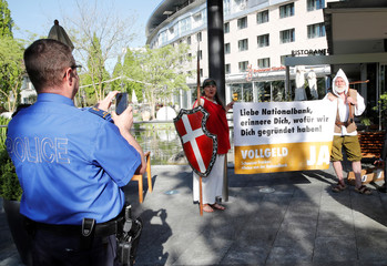 A policeman takes a pictures of members of the sovereign money initiative dressed as Helvetia and William Tell, during a demonstration outisde the Shareholders meeting of the Swiss National Bank (SNB) in Bern