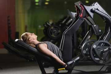 Sportive woman using weights press machine for legs at the gym. Pretty brunette exercising in a simulator. Working her quads at machine.