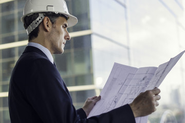 Man wearing hard hat reviewing blueprint