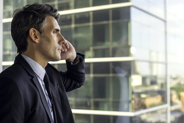 Man looking through window in high rise building