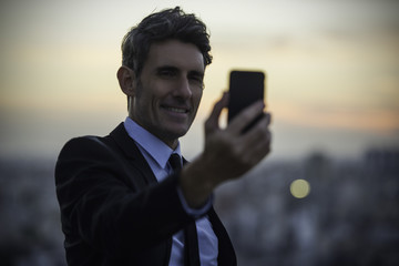 Businessman taking selfie with mobile phone