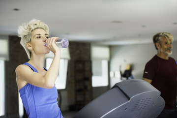 Woman drinking water while exercising on treadmill