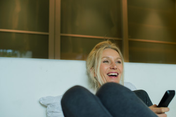 Mature woman laughing while watching TV
