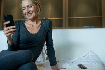 Mature woman sitting on bed, looking at smartphone and smiling