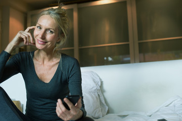 Mature sitting on bed with smartphone in hand, smiling, portrait