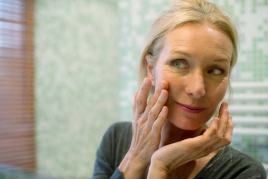 Mature woman looking at reflection in mirror with hand on cheek