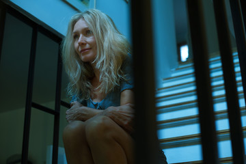 Mature woman sitting on stairs, looking away in thought