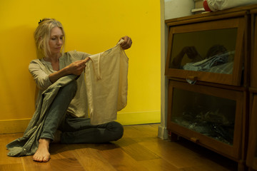 Mature woman sitting on floor looking at shirt with unhappy expression