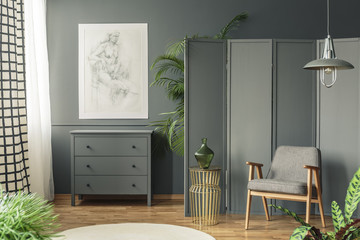 Dark, gray living room interior with a sketch hanging above a wooden chest of drawers next to a screen, golden table and armchair Wall mural