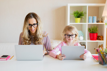 Mom and daughter using modern tech together