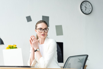 portrait of businesswoman in white suit and eyeglasses at workplace with laptop in office