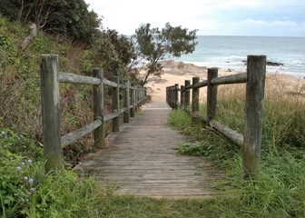 Wooden path to beach in Australia. Ramp for beach access. Wooden pillars supporting the ramp on sand at Australian beach.