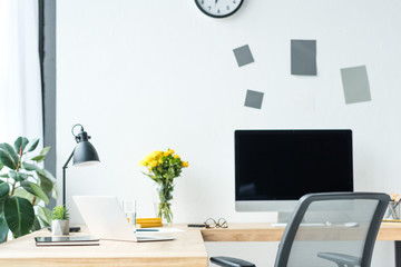 close up view of empty workplace with blank computer screen, laptop, eyeglasses and bouquet of chrysanthemum flowers in office