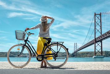 Blonde woman in summer hat and yellow skirt with her city bicycl
