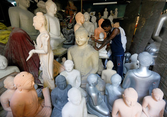 A man cleans a Buddha statue, intended for sale, before taking it to a paint room ahead of Vesak Day celebrations at a factory in Colombo