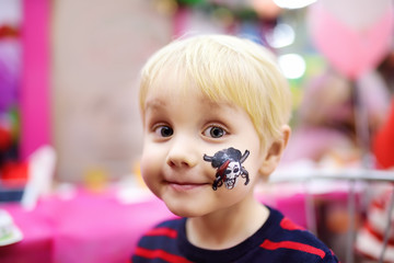 Face painting for cute little boy during kids birthday party
