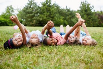 Multikulturelle Gruppe Kinder liegt auf Wiese