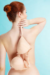 Naked woman holds beige bra in hand