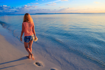 Blonde woman is walking by the sea at sunset