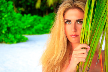 Beautiful blonde woman looks between palm leaves on the sandy beach at the camera
