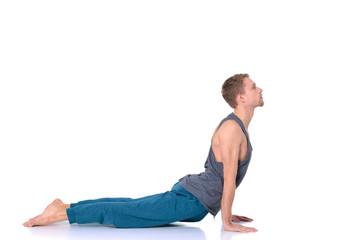Adult man doing yoga exercise on white background