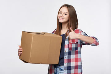 Delivery, relocation and unpacking. Happy playful young woman holding cardboard box gesturing thumb up