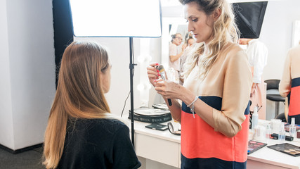 Professional makeup artist standing at young model in beauty salon