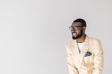 portrait of handsome young african american man in eyeglasses smiling and looking away isolated on grey