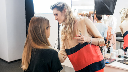 Professional makeup artist working with young model in studio before fashion show