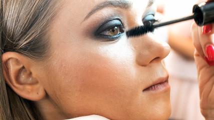 Closeup image of makeup artist applying smokey eyes makeup