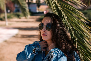 teen girl with sunglasses under a palm tree in a park