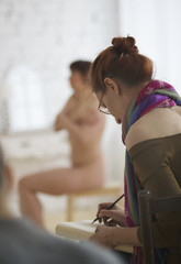 Female young painter who sketching nude model in a workshop