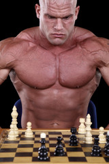 Bodybuilder playing chess in front of black background