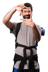 Handsome backpacker focusing with his fingers on white background