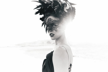 Black and white dramatic portrait of beautiful young woman in dress with black flowers and with...
